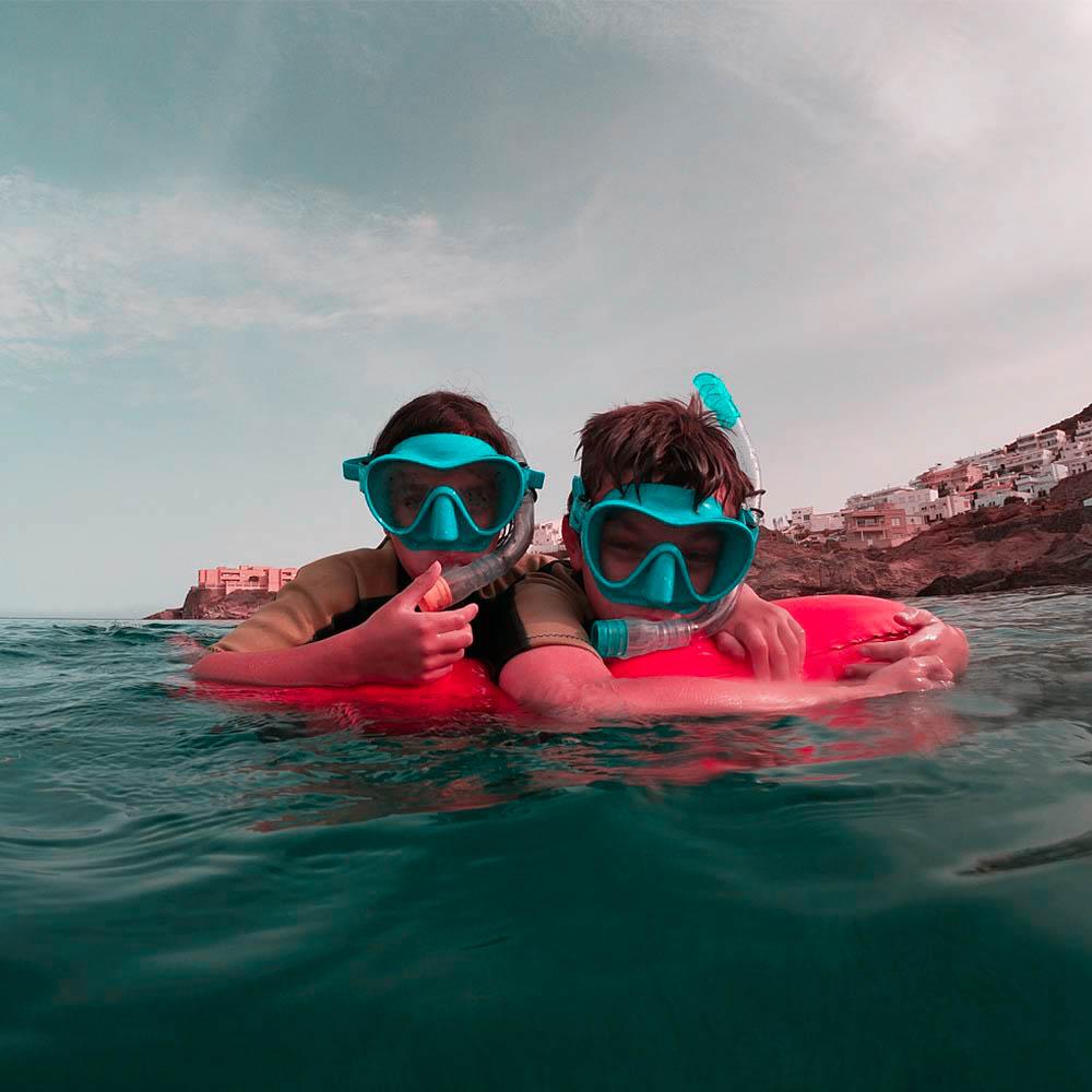 Niños haciendo en snorkel en cabo de gata subidos en una boya de playa